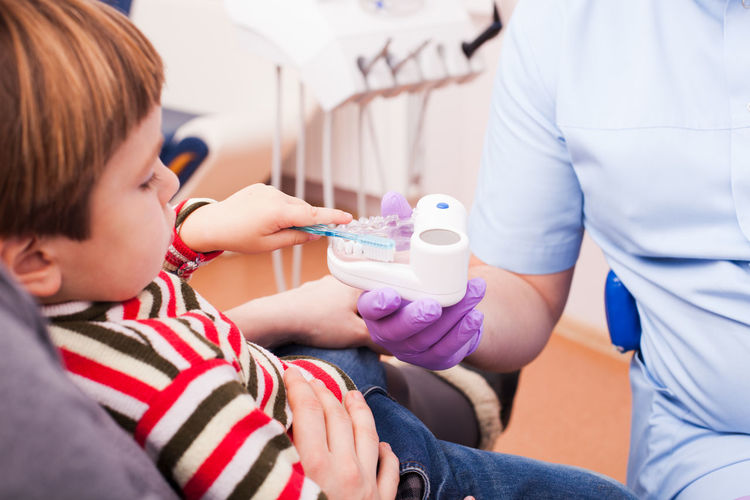 Child brushing teeth model at dental clinic