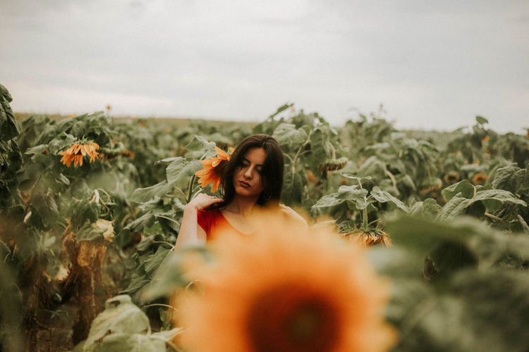 Woman Standing Amidst Sunflower Plants Against Sky