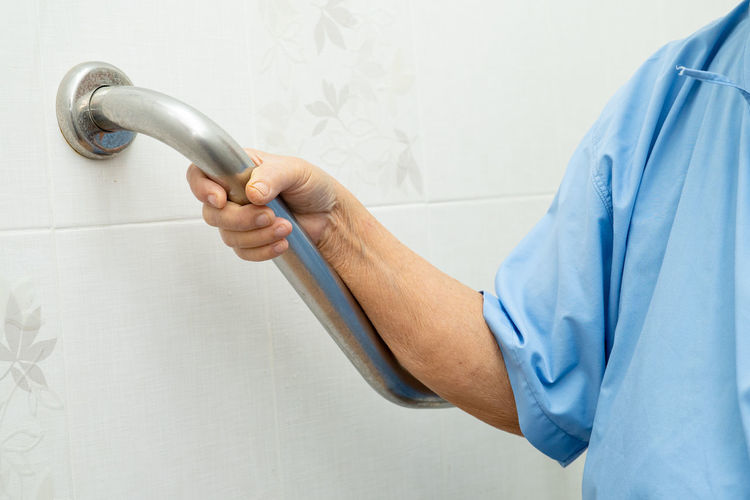 Midsection of senior woman holding railing by wall at bathroom