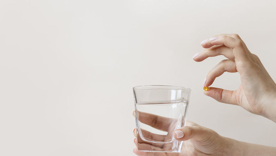 Midsection of woman holding glass against white background