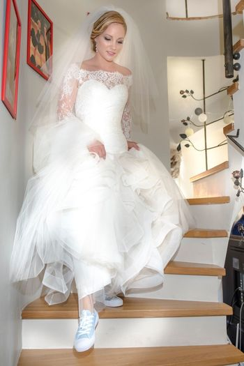 Full length of bride moving down staircase