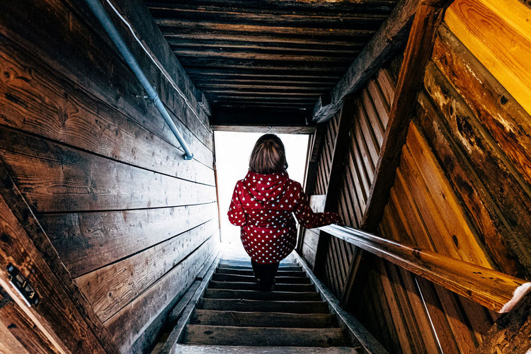 Rear view of woman standing on staircase