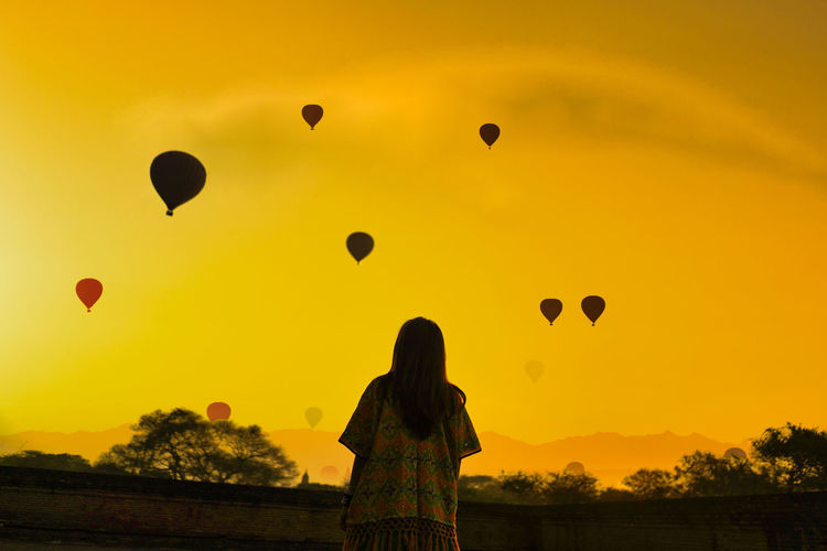 Rear view of woman standing by wall against sky with hot air balloon during sunset