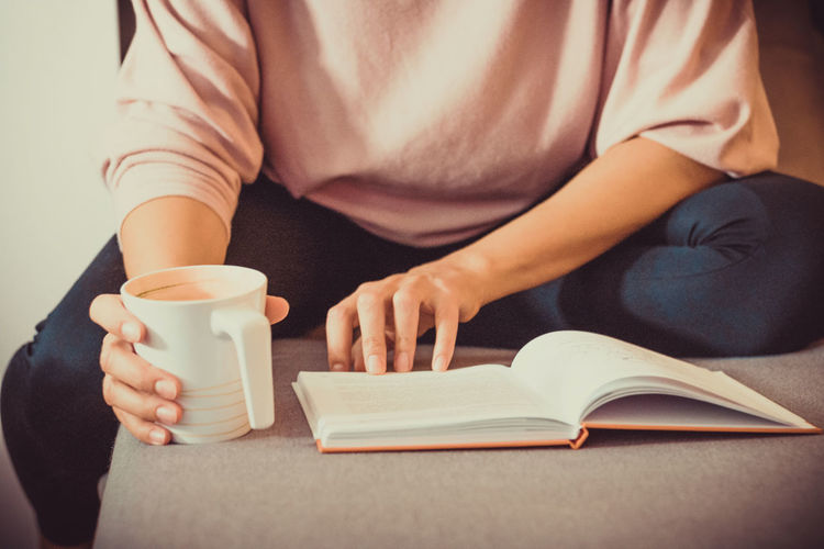Unrecognizable woman drinking coffee and reading book while relaxing at home.