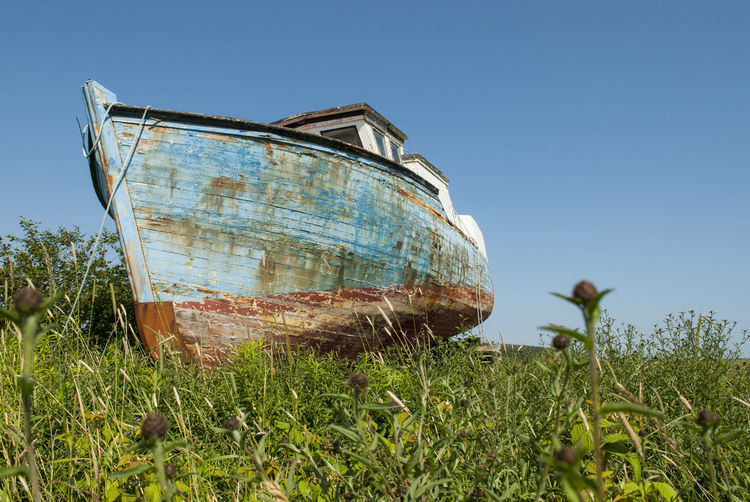 Abandoned boat on field against clear sky