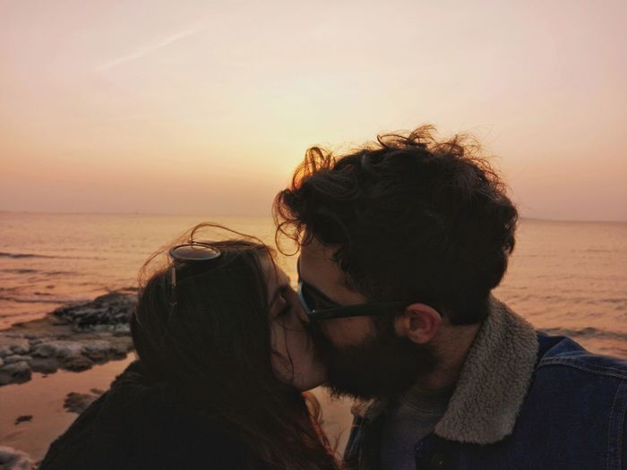 Close-up of couple kissing against sea during sunset