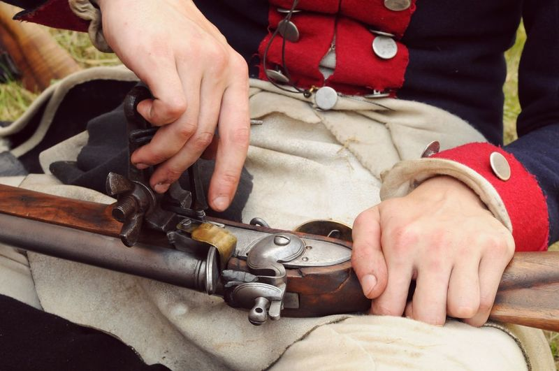 Cropped Image Of Man Cleaning Gun At Field