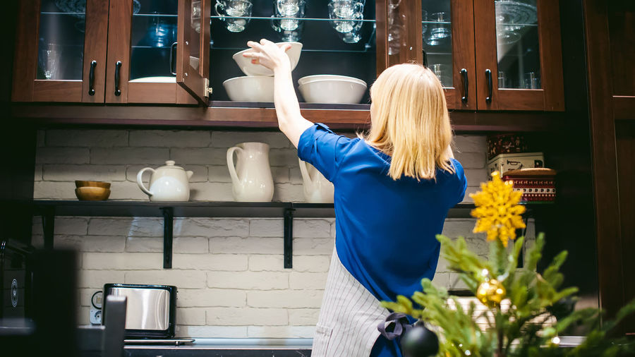 Rear view of woman preparing food in kitchen