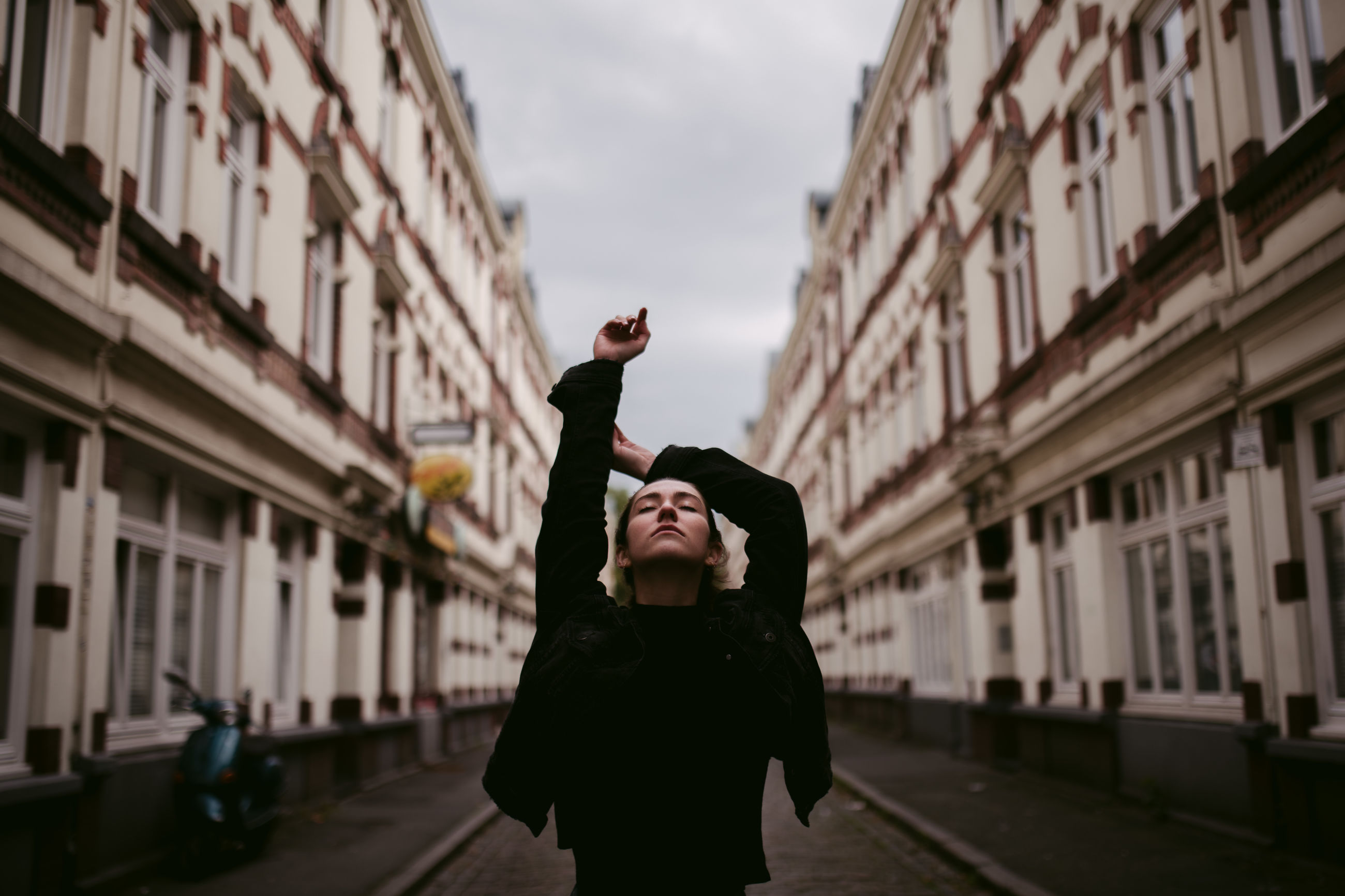 one person, building exterior, architecture, real people, city, built structure, lifestyles, leisure activity, standing, day, focus on foreground, street, young adult, three quarter length, building, nature, photography themes, adult, women, outdoors, arms raised, human arm