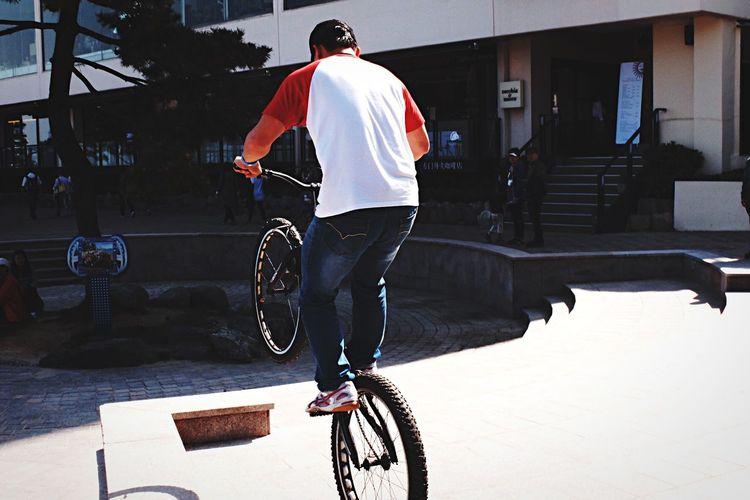 Rear View Of Biker Performing Stunt On Road