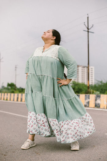 Full length of woman standing on road against sky in city