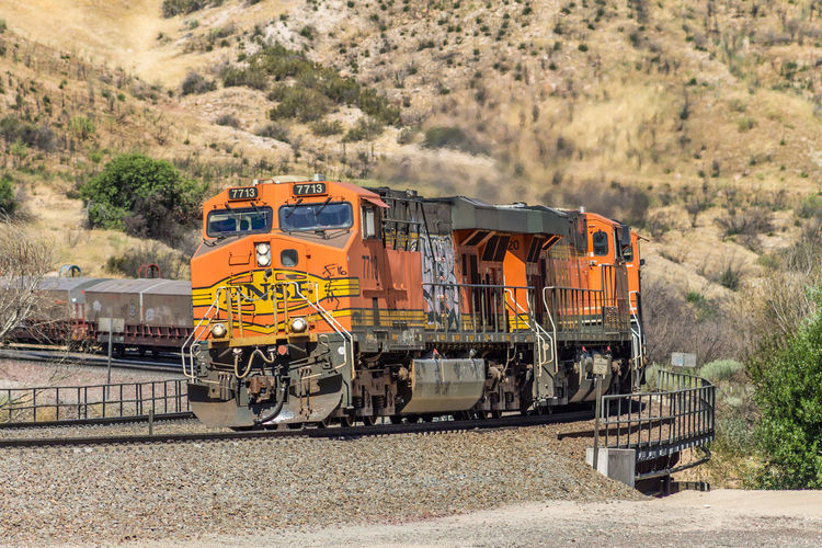 BNSF 7713 leading a westbound manifest down Cajon Pass BNSF Trains Cajon Pass Curve Graffiti Manifest Day Locomotive Mode Of Transport Outdoors Rail Transportation Railroad Railroad Track Train Train - Vehicle Transportation