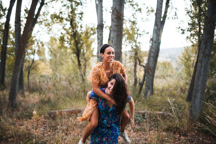 Woman piggybacking girlfriend in forest