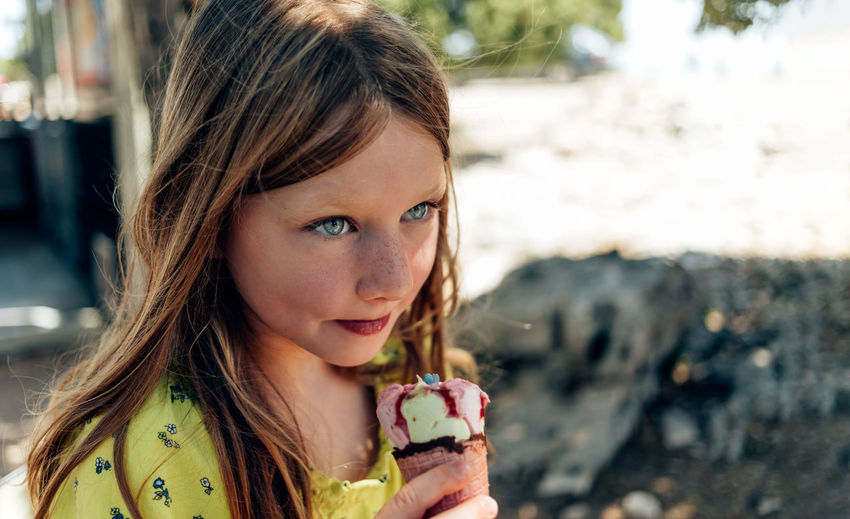 Young girl having fun eating ice cream outdoor during hot summer vacation - focus on kid face