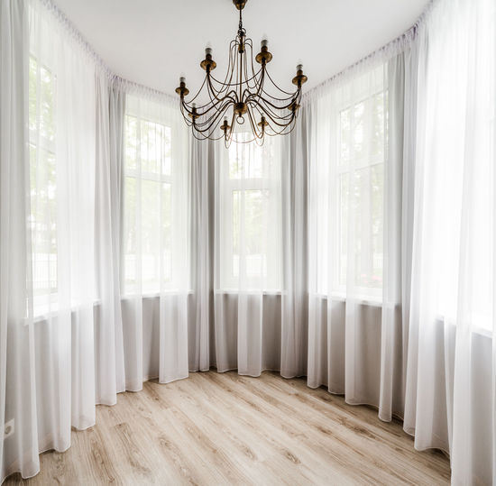 Elegant room interior with wooden floor, white curtain and chandelier Ceiling Elegant Room Chandelier Curtains Day Daylight Design Domestic Room Empty Room Floorboard Hanging Chandelier Home Interior Indoors  Interior No People Nobody Parquet Floor Space Symmetry Unfurnished White And Beige White And Brown Window Wooden Floor