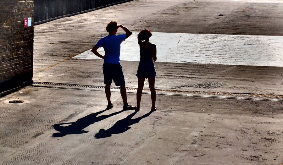 Looking into the Sun Alone Beach Carefree Friendship Full Length Horizon Over Water Leisure Activity Lifestyles Real People Rear View Sand Sea Shore Standing Togetherness Two People Man Woman Shadows Looking Into Sun On Rooftop Concreet Car Park Multistory Cinema Peckham South London England Uk Sunshine Shorts Hot Warm Vacations Walking Women Pmg_lon