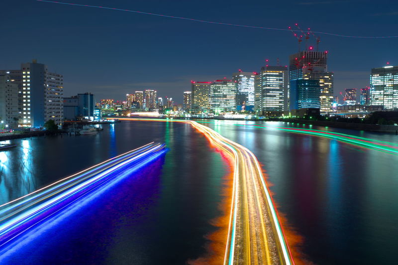 Illuminated light trails amidst buildings in city at night