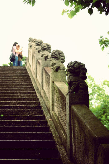 Low angle view of woman on staircase against sky