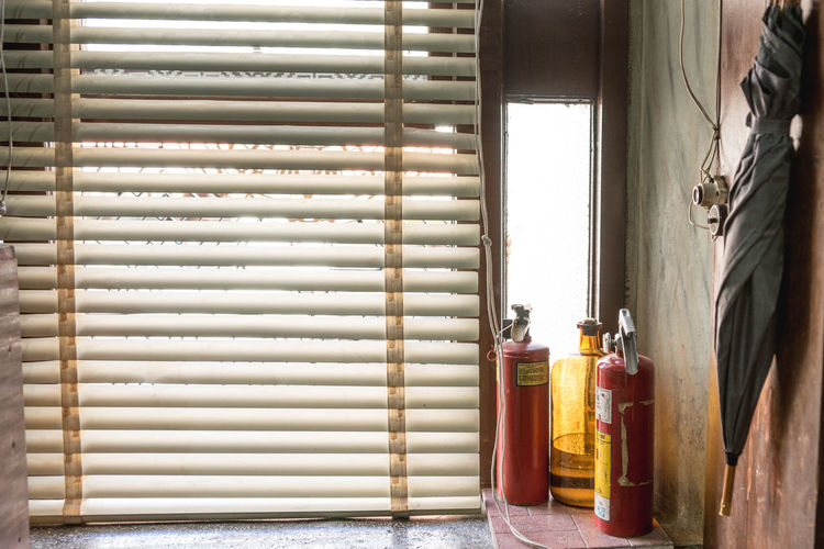 Fire extinguishers by blinds in room