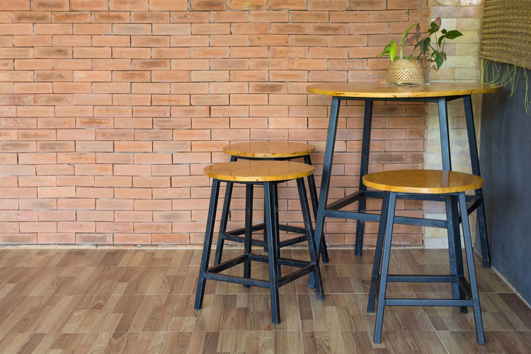 wood chair and table on brick wall Seat Chair Table Indoors  Furniture Brick Brick Wall Home Interior Flooring No People Absence Wood - Material Wall - Building Feature Wall Domestic Room Food And Drink Wood Stool Dining Room Hardwood Floor Flower Pot