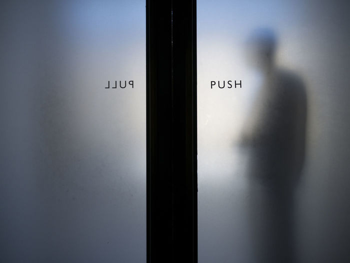 Silhouette of a man behind opaque glass doors. Close-up Day Door Doorway Glass Door Indoors  Pull Push Silhoutte Sliding Door Secret Places The Spaces