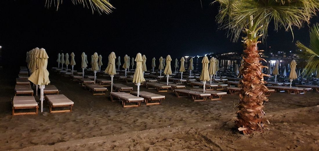 Panoramic view of people on beach against sky at night