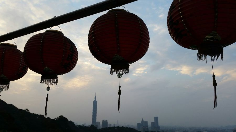 Low angle view of lanterns against cloudy sky