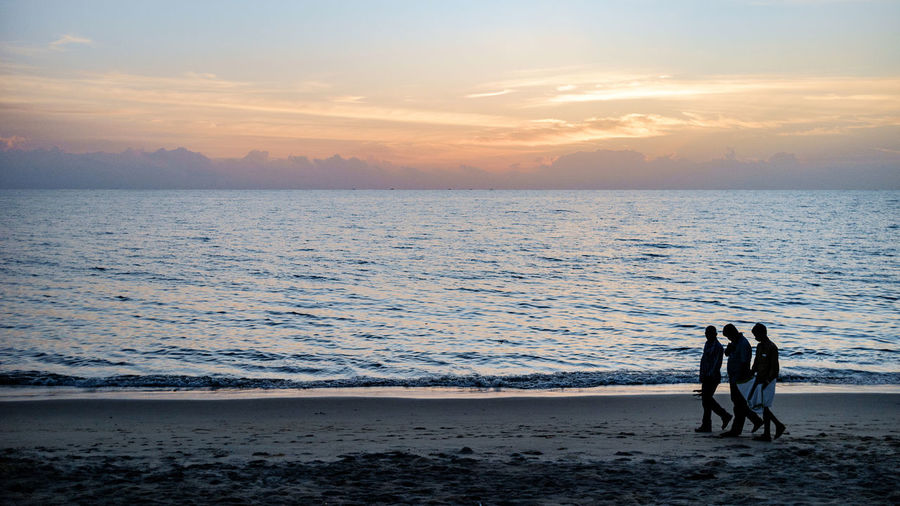 Men Walking At Beach Against Sky During Sunset