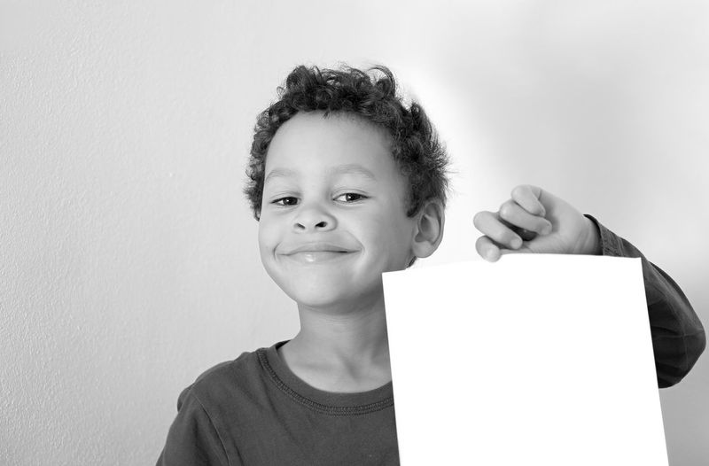 Portrait of smiling boy holding paper against wall