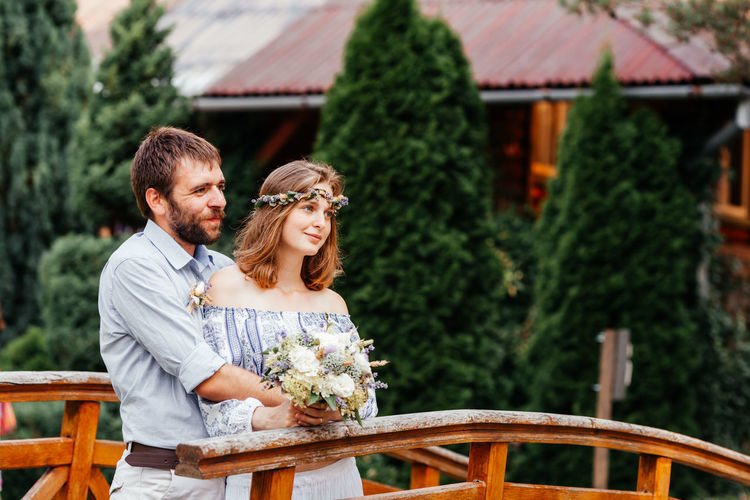 Couple holding bouquet standing outdoors