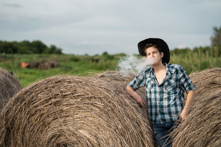 Portrait of a handsome young man in a cowboy hat vaping an electronic cigarette near the haystack.