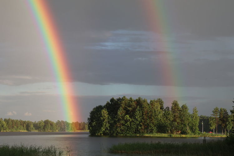 Scenic view of lake against rainbow in sky
