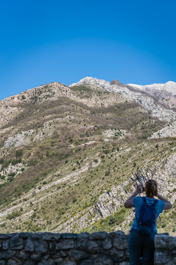 Rear view of woman photographing mountain against blue sky