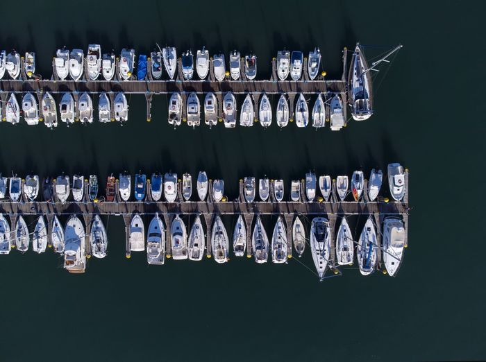 Panoramic aerial view on boats moored in the pier, drone shot directly above. luanco in asturias