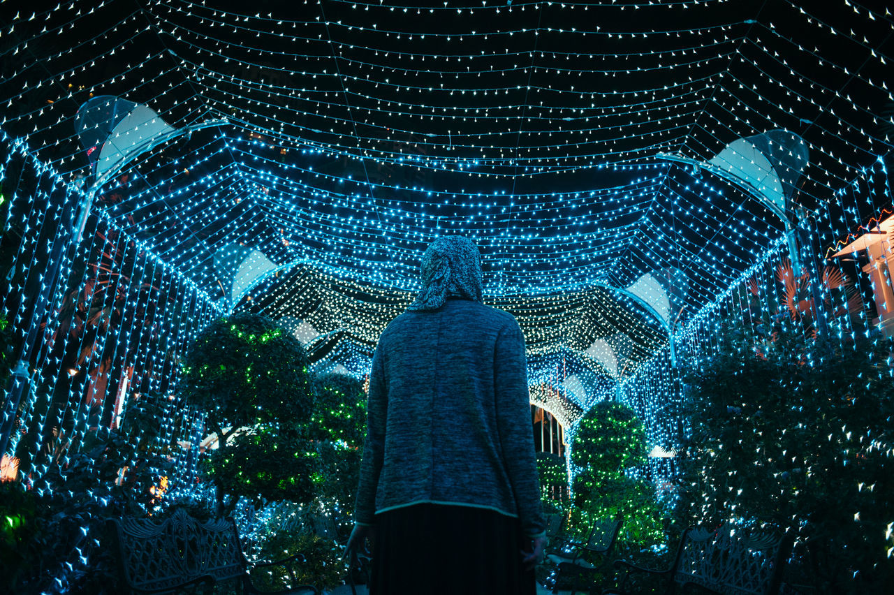 Low angle view of person standing against illuminated lights at night