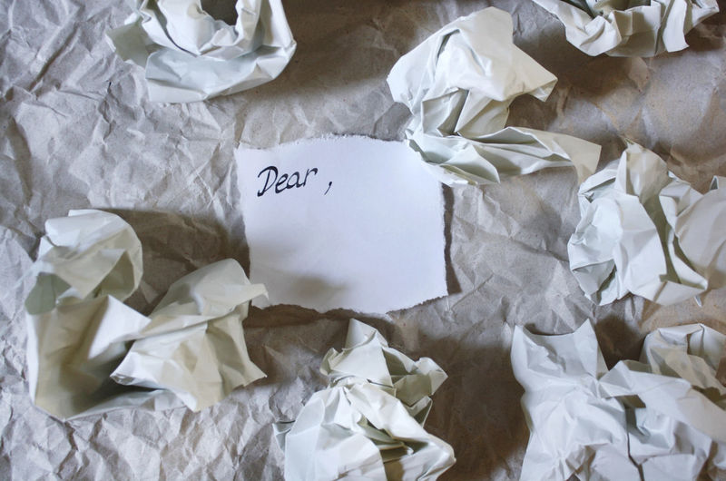 High angle view of dear text by crumpled paper on table