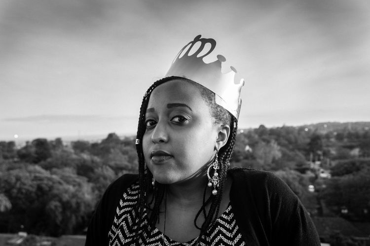 Portrait of young woman with crown against sky