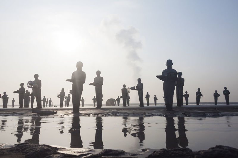 Group of people at beach against sky