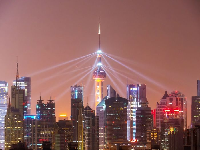 Illuminated Oriental Pearl Tower Amidst Buildings In City At Dusk