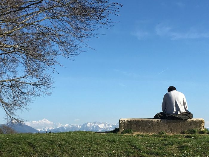 Rear view of man sitting on retaining wall against sky