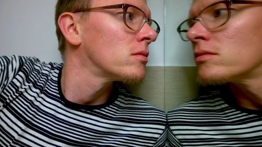 Close-up of serious man with mirror reflection at home