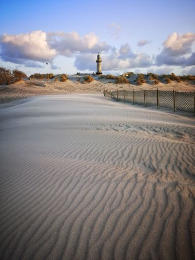 View of sand dunes at beach against sky