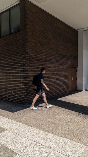 Full length of man on footpath against wall