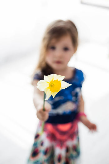 Close-up of girl with flowers against white background
