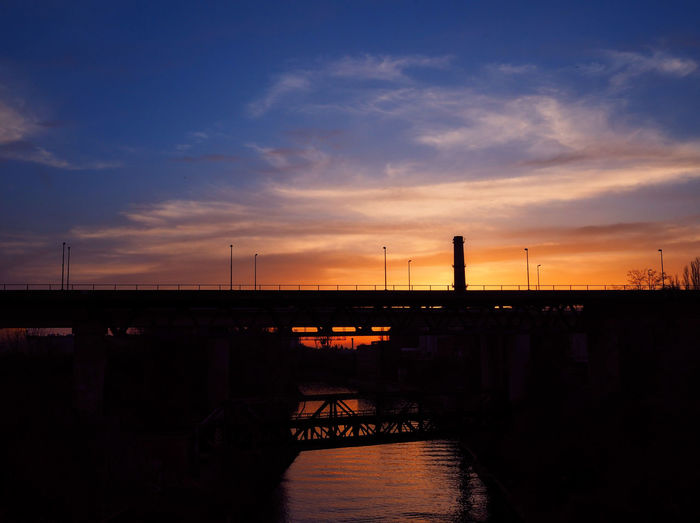 Silhouette factory by river against sky during sunset