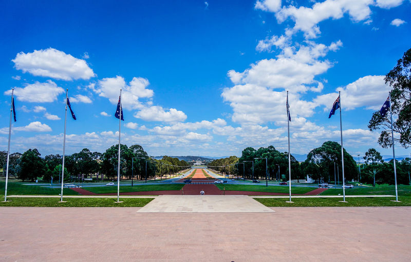 Australian flags at park with walkway leading towards parliament house against sky