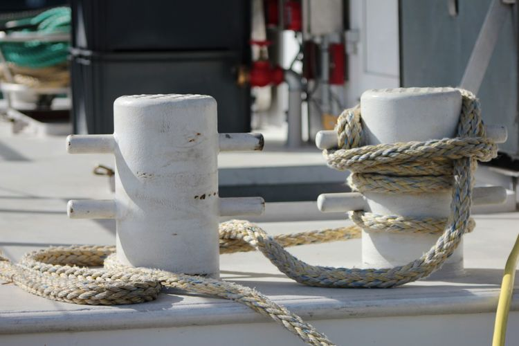 Close-up of ropes tied to bollards
