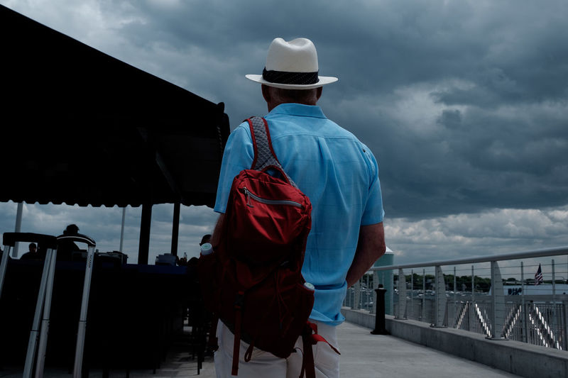 Rear View Of Man On Pier Against Cloudy Sky