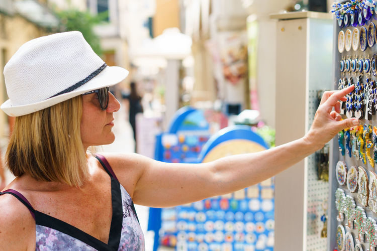 Woman wearing hat buying souvenir in city