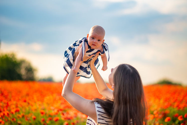 Mother picking up cute daughter amidst plants against sky